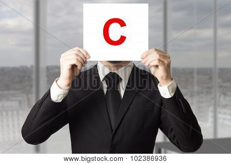 businessman holding up sign with letter c