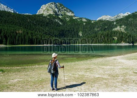 Woman Hiker With A Backpack And Walking Stick On The Black Lake In Durmitor National Park, Montenegr