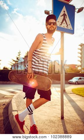 Stylish Man In Sunglasses With A Skateboard On A Street In The City At Sunset Light