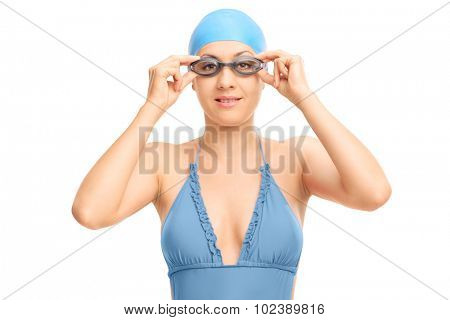 Female swimmer in a blue swimsuit adjusting her goggles and looking at the camera isolated on white background