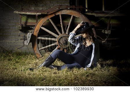 Sexy farm girl in denim with hat resting against old wagon wheel
