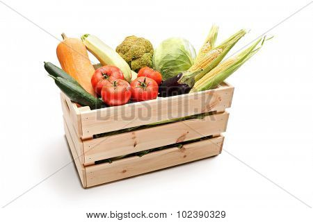 Studio shot of a wooden crate full of different types of fresh vegetables isolated on white background