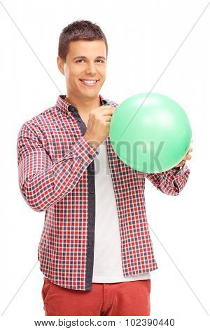 Vertical shot of a cheerful young man blowing up a green balloon and looking at the camera isolated on white background