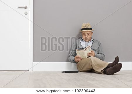 Senior gentleman reading a book seated on the floor and leaning against a wall next to a white door