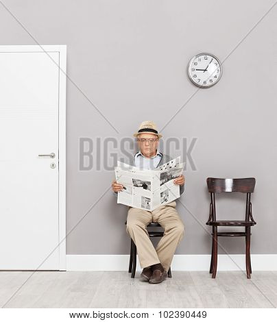 Senior gentleman sitting on wooden chairs in a waiting room and reading a newspaper shot with tilt and shift lens