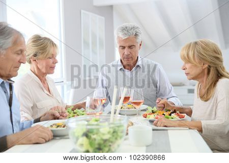 Group of people giving blessings before eating