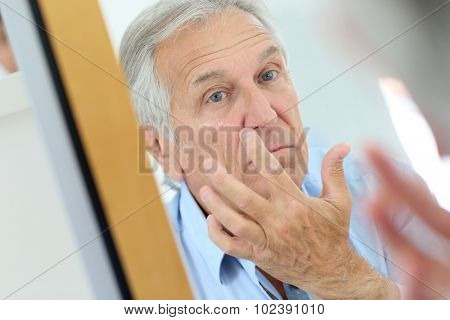Senior man applying anti-aging lotion on his face
