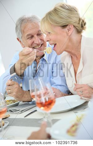 Senior couple sharing pasta at lunch time