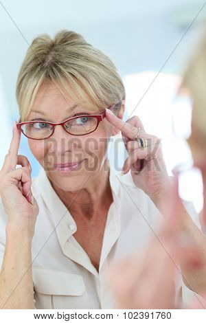 Elderly woman trying eyeglasses on in front of mirror