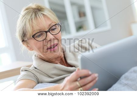 Senior woman with eyeglasses using digital tablet at home