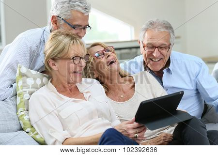 Group of senior friends with eyeglasses using digital tablet