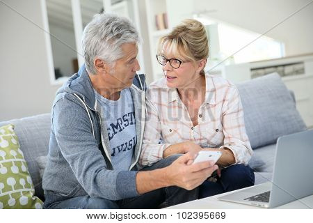 Senior couple at home websurfing on laptop computer