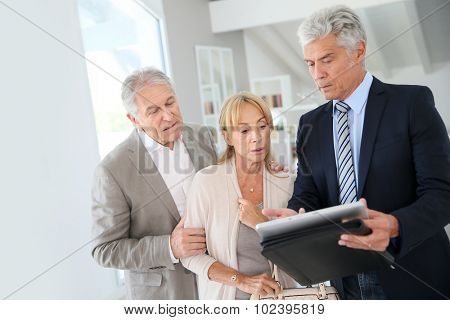 Senior couple with real-estate agent visiting house for sale