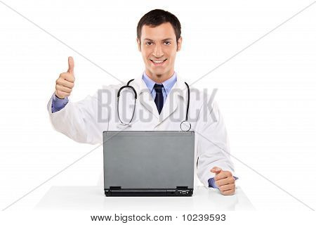 Happy Doctor With Thumb Up Working On A Laptop