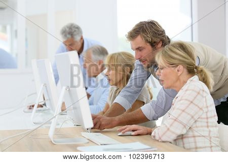 Instructor helping senior woman in computing class
