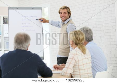 Business instructor leading meeting with senior training group