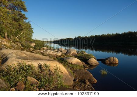 Beautiful stony coast of the northern river in the evening.
