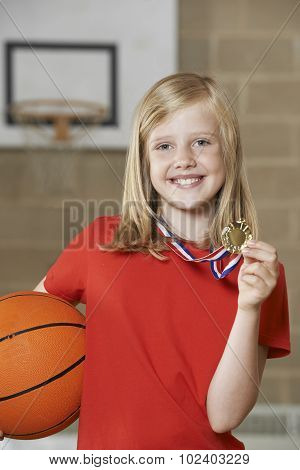 Girl Holding Basketball And Medal In School Gymnasium