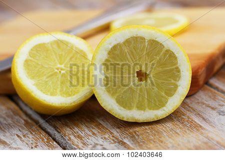 Half lemon leaning against wooden board