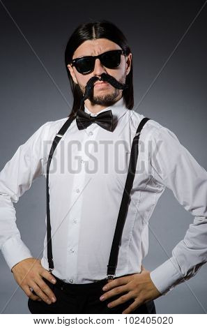 Man with moustache and sunglasses against gray