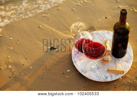 Wine bottle and glasses on sand background