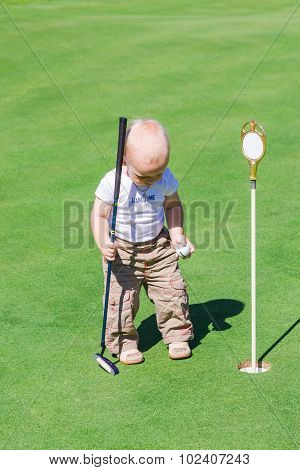 Cute Little Baby Boy Playing Golf On A Field