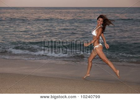 Woman Running On Beach In A White Bikini