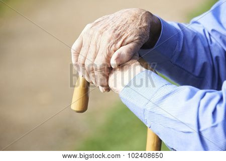 Close Up Of Senior Man's Hands Resting On Walking Stick
