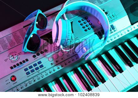 Headphones with sunglasses on synthesizer close up