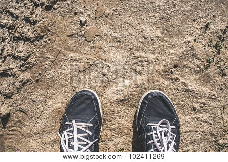 First person perspective of blue walking shoes on muddy road