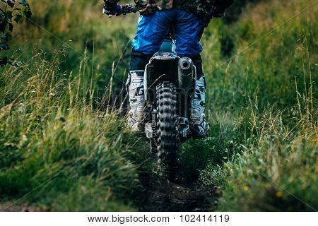 motocross racer is riding on a footpath