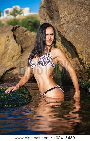 Women Athlete on a rock by the sea