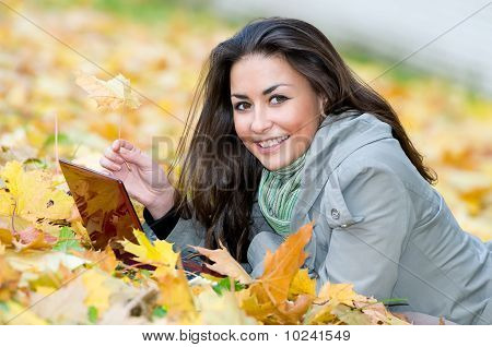 Happy Student Girl Lying In Autumn Leaves With Netbook
