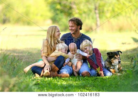 Parents Looking Lovingly At Each Other With Famil And Dog
