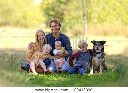 Happy Young Family Relaxing Outside With Pet Dog