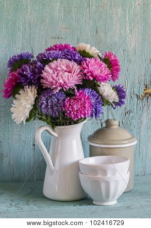 Flowers Asters In A White Enameled Pitcher And Vintage Crockery - Ceramic Bowl And Enameled Jar, On