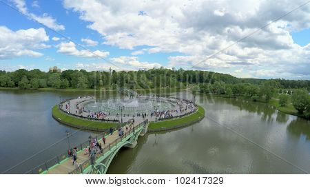 MOSCOW - JUN 06, 2015: Many people walk by West arch bridge to Horseshoe island with Sound and Color Light Fountain at summer day. Aerial view
