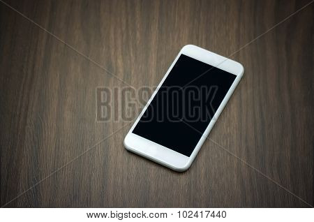 Smart Phone With Blank Screen On Wooden Table