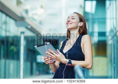 Young Woman Using Digital Tablet  And Listening Music