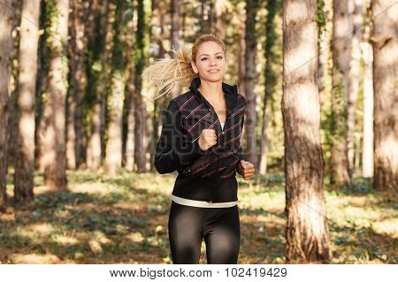 Beautiful Young Woman Running Through The Park