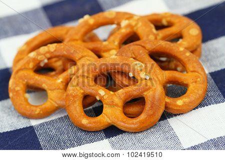Salty pretzels on checkered cloth, closeup