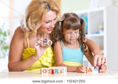 kid and mother building the word mama playing wooden cubes