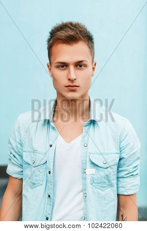 Close-up Portrait Of A Young Stylish Guy In A Denim Shirt Near A Blue Wall.