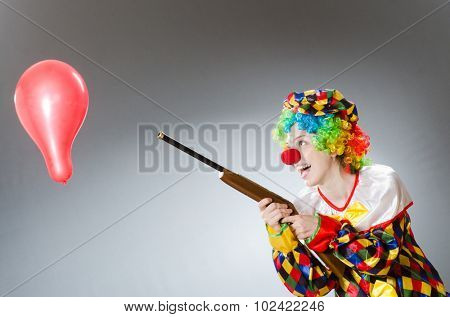 Clown with balloon and rifle in funny concept