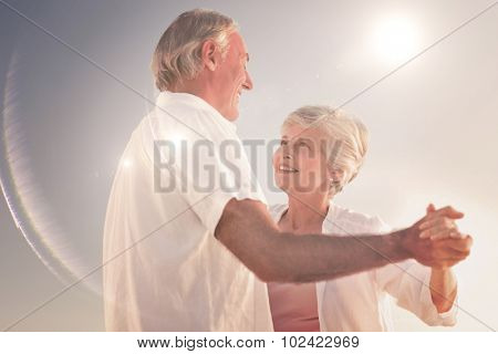 Senior couple dancing on the beach against light beam
