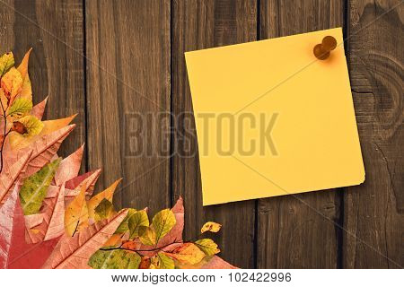 Yellow pinned adhesive note against autumn leaves on wood
