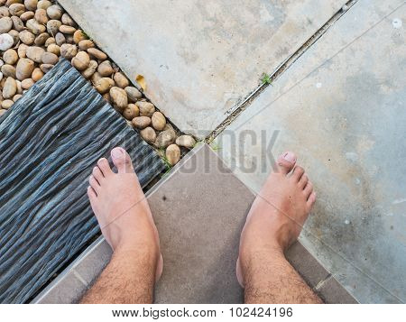 A Man Look Down To His Bare Feet, Stand On The Multiple Texture Floor.