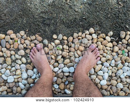 A Man Look Down To His Feet, Stand On The Rocks.