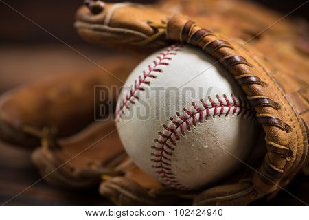 Brown leather baseball glove on a wooden bench