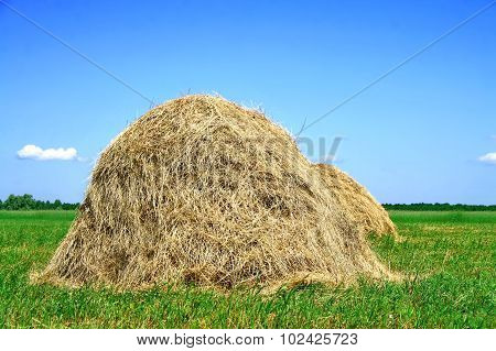 Photo of two haystacks over blue sky